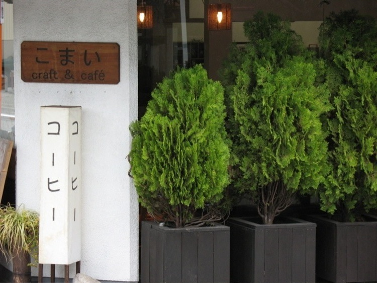 A picture of bushes and a sign for a coffee shop in Japan.
