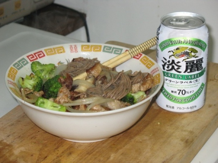 A bowl filled with stirfry, and a can of beer.