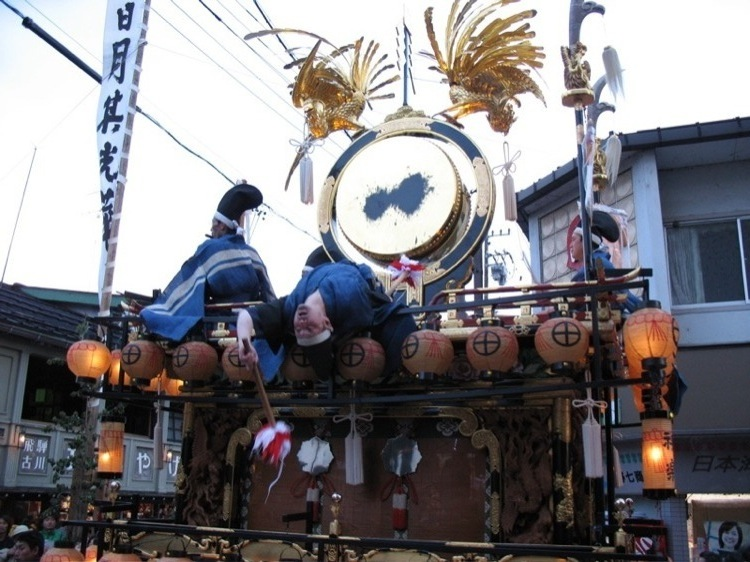 A drummer leaning backwards on top of a float.