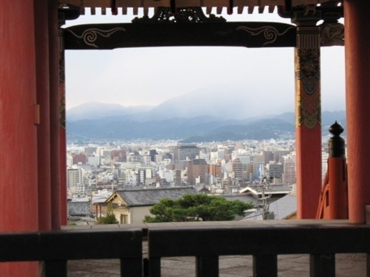 A picture taken through an arch of the Kyoto skyline